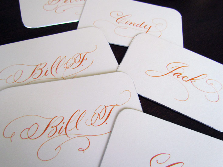 Flourished Script Calligraphy Place Cards in orange Ink